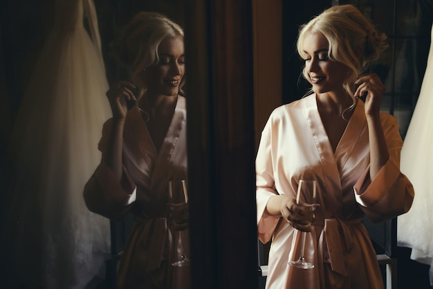 Stunning blonde lady in silk robe stands with glass of champagne