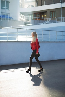 Stunning blonde model wearing red jacket walking down the street with sun light