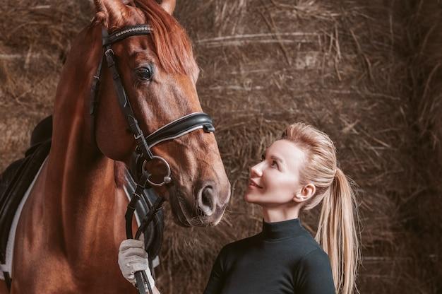 サラブレッド種の馬とポーズをとる見事な金髪。牧場休暇のコンセプト。ミクストメディア