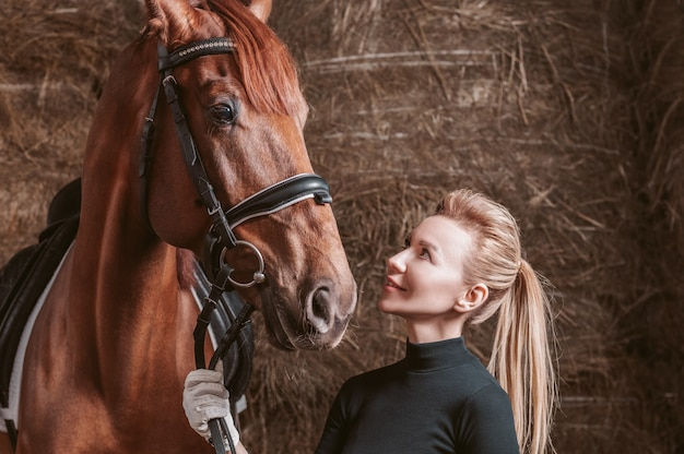 Stunning blonde posing with a thoroughbred horse. ranch vacation concept. mixed media