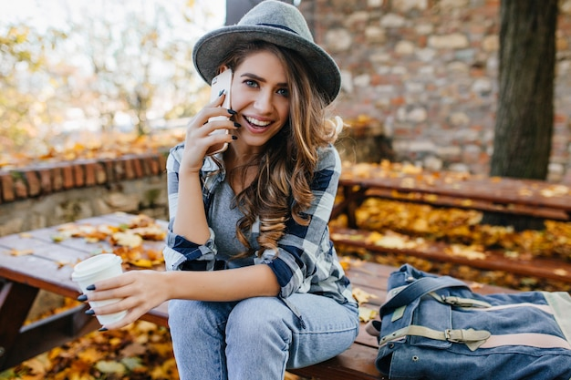 Stunning blue-eyed lady with curly hairstyle calling friend in good autumn day