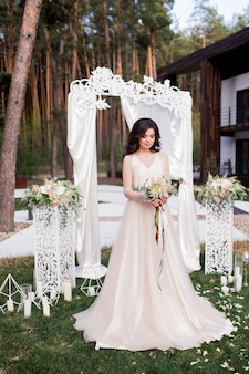 Stunning bride in a beige dress stands before a wedding altar outside