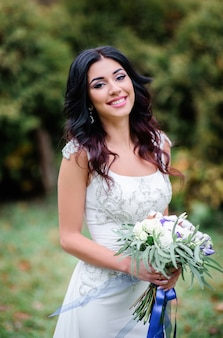 Stunning bride in dress with silver embroidery stands on green lawn
