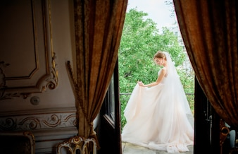 Stunning bride in a wedding dress poses on the balcony in a luxury hotel room