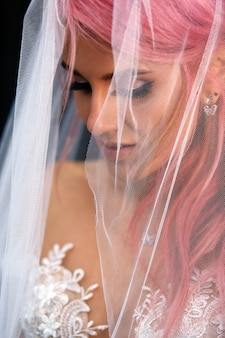 Stunning bride with pink hair covered with light veil