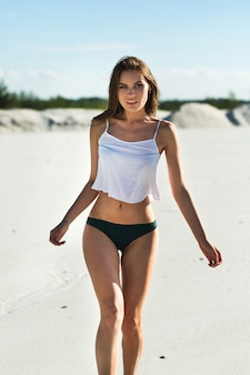 Stunning brunette with long hair poses in white top on the beach