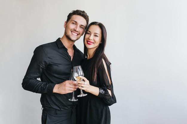 Сногсшибательная брюнетка чокается с красивым мужем во время вечеринки друга
