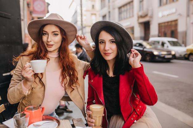 Потрясающая брюнетка женщина в серой шляпе проводит время с рыжей подругой в кафе
