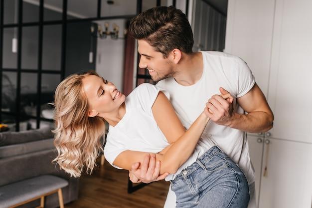 미소로 남자 친구를 찾고 멋진 백인 소녀. 남편과 함께 춤을 추는 화려한 젊은 여자의 실내 초상화.