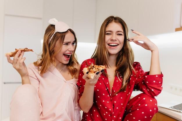 아침 식사 중에 아침에 장난 치는 멋진 백인 소녀. 피자를 먹고 사랑스러운 자매 웃음의 실내 샷.