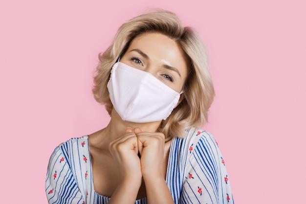 顔に医療マスクを身に着けているピンクのスタジオの壁に喜びを身振りで示す見事な白人女性