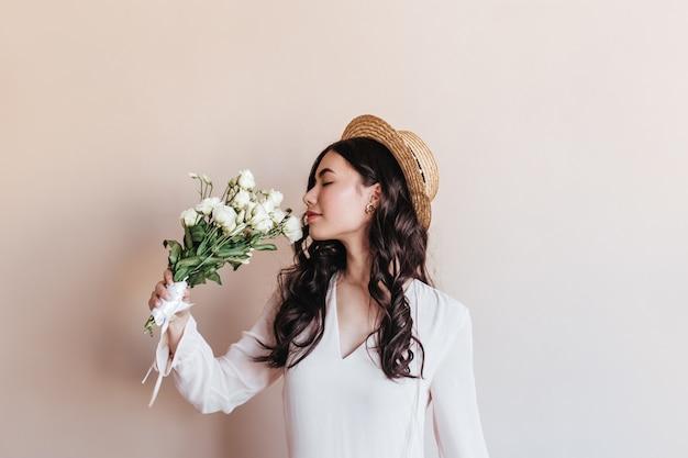 白い花を嗅ぐ見事な巻き毛のアジアの女性。トルコギキョウとロマンチックな中国の女性のスタジオショット。