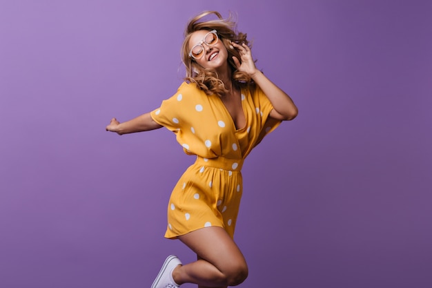 Stunning curly female model jumping on purple. indoor portrait of slim girl in bright yellow dress.