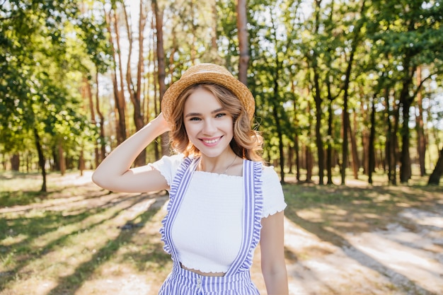 아름다운 미소로 숲에서 포즈를 취하는 멋진 곱슬 소녀. 화창한 아침에 공원에서 재미 사랑스러운 젊은 아가씨의 야외 촬영.