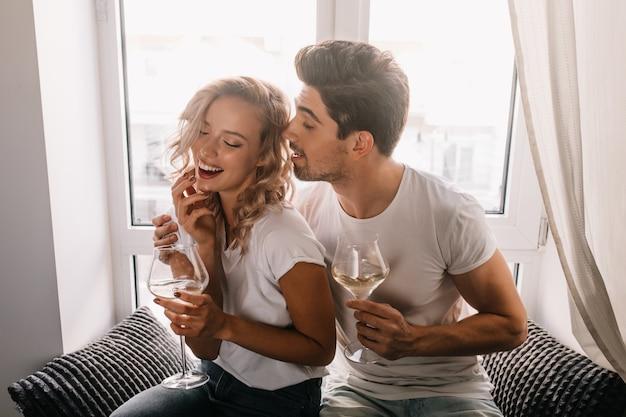 남자 친구와 데이트를 즐기는 멋진 곱슬 여자. 기념일에 샴페인을 마시는 행복 한 커플.