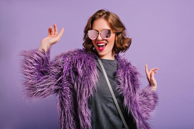 Потрясающая милая девушка с вьющимися каштановыми волосами с удовольствием позирует на фиолетовом фоне