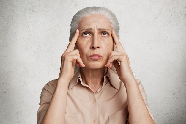 Stunning elderly woman against concrete wall