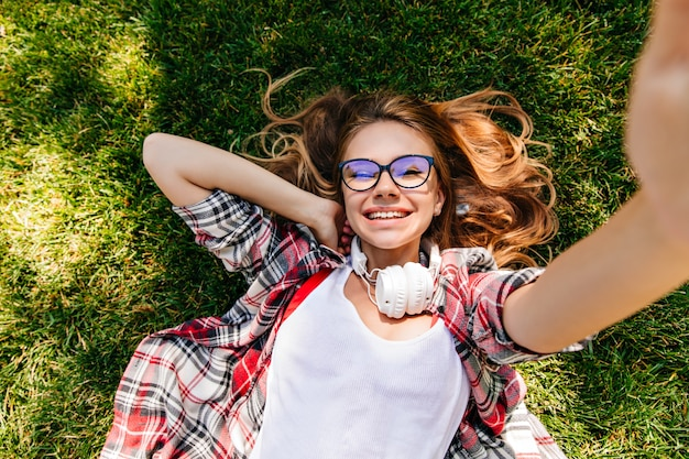 Stunning european girl lying on grass and laughing. pleasant young woman posing in park with cheerful smile.