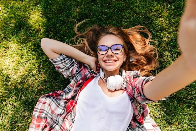 草の上に横たわって笑っている見事なヨーロッパの女の子。陽気な笑顔で公園でポーズをとる楽しい若い女性。