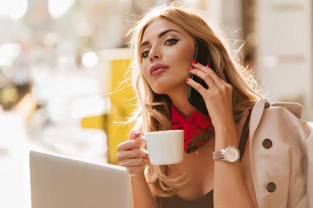 見事なヨーロッパの女の子はお茶のカップを保持している見上げる黄金のペンダントを着ています。