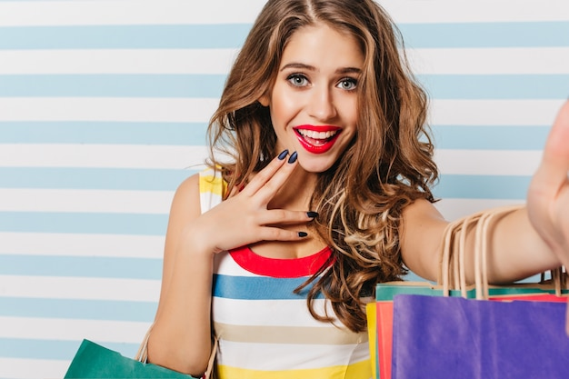 Потрясающая европейская девушка с голубыми глазами, расслабляясь во время покупок. фотография в помещении модной красивой дамы с сумками из магазина.