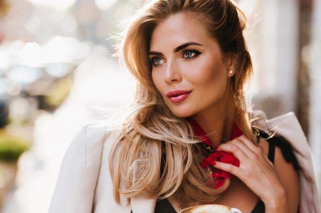 Splendida ragazza europea con trucco glamour che guarda lontano toccando la sua sciarpa rossa. ritratto del primo piano di bella donna bionda con gli occhi azzurri rilassante