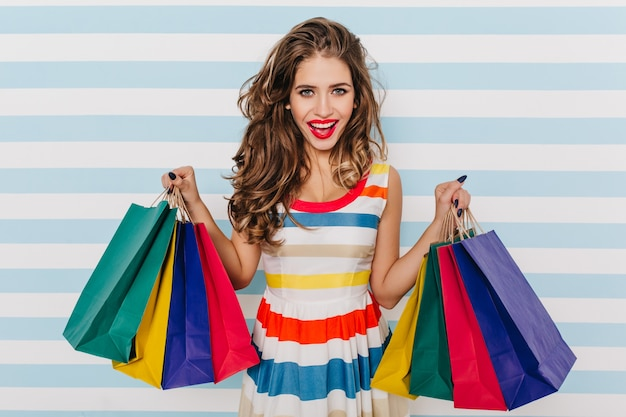 Сногсшибательная европейская женщина покупает летнюю одежду. портрет очаровательной женской модели с новыми покупками.