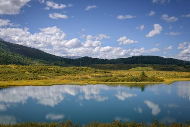Потрясающий сказочный вид с берега горного озера в солнечный день. зеленые холмы, синяя поверхность воды отражает небо с белыми облаками.