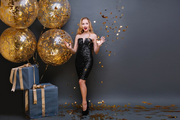 Stunning fair-haired european woman throwing out sparkle confetti while posing. adorable caucasian birthday girl standing with big gift boxes and waving hands with smile.