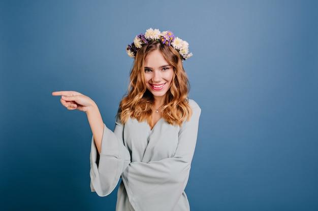 Splendida donna bionda in ghirlanda di fiori in posa con un sorriso giocoso