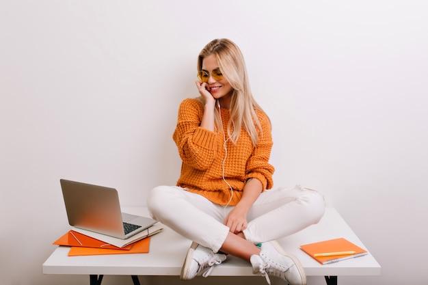 笑顔でテーブルでリラックスし、ノートパソコンの画面を見ているカジュアルな服装で見事な女性モデル