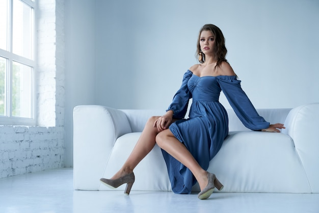 Stunning female model wearing blue midi dress with wide neckline, heels and earrings looking aside.