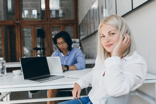 Stunning female programmer playing with blonde hair while posing at workplace with asian male colleague. busy chinese web-developer working with laptop sitting at the table with white secretary girl.