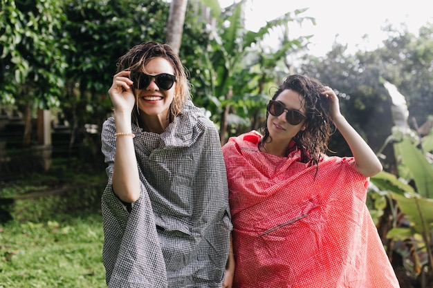비 후 포즈를 취하는 젖은 머리를 가진 멋진 여성 관광객. 선글라스와 자연에 서있는 비옷에 웃는 여행자의 야외 초상화.