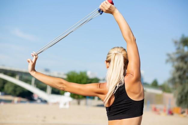 縄跳びでストレッチをする完璧なスリムボディの見事なフィットネスモデル。空きスペース