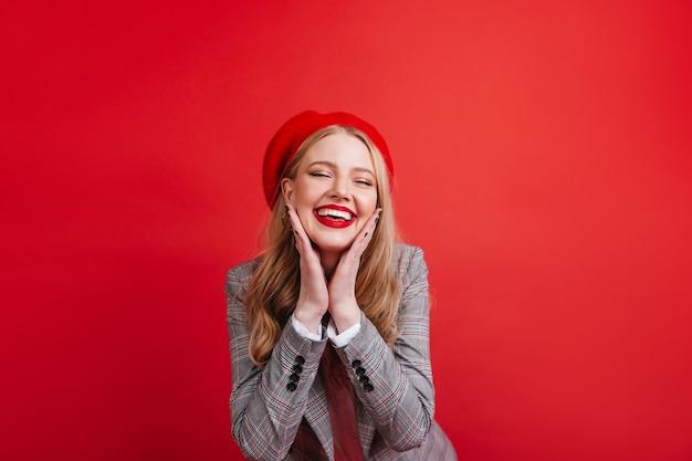 빨간 벽에 포즈를 취하는 멋진 프랑스 소녀. 웃 고 기쁜 금발의 젊은여자가