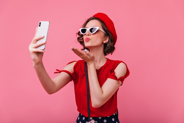 Splendida donna francese che manda un bacio d'aria mentre si scatta una foto. ritratto dell'interno della signora riccia romantica in betet che fa selfie.