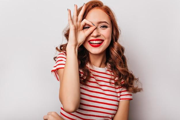 Сногсшибательная рыжая девушка с волнистой прической, выражающая счастье. заинтересованная молодая женщина в полосатой одежде весело на белой стене.