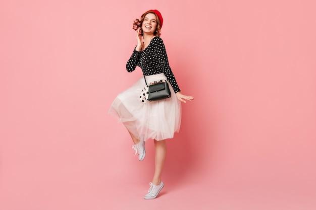ピンクの背景で踊り、カメラを見ている見事な女の子。ベレー帽とスカートのロマンチックなフランス人女性の完全な長さのビュー。