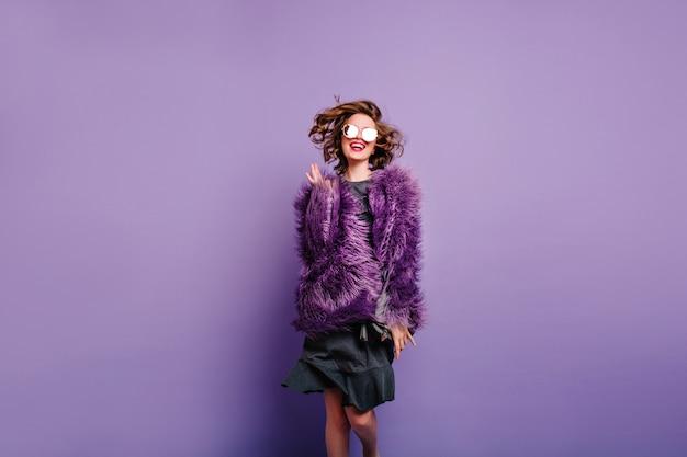 Splendida ragazza di buon umore che salta su sfondo viola e sorridente