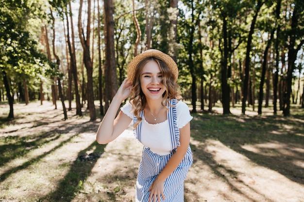 숲에서 촬영하는 동안 웃 고 유행 복장에 멋진 소녀. 공원에서 좋은 하루를 즐기고 모자에 사랑스러운 여성 모델.