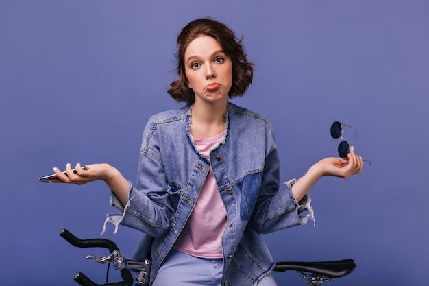 아름 다운 보라색 벽에 포즈 유행 재킷에 멋진 여자. 자전거 근처에 앉아 평온한 곱슬 여자의 실내 사진.