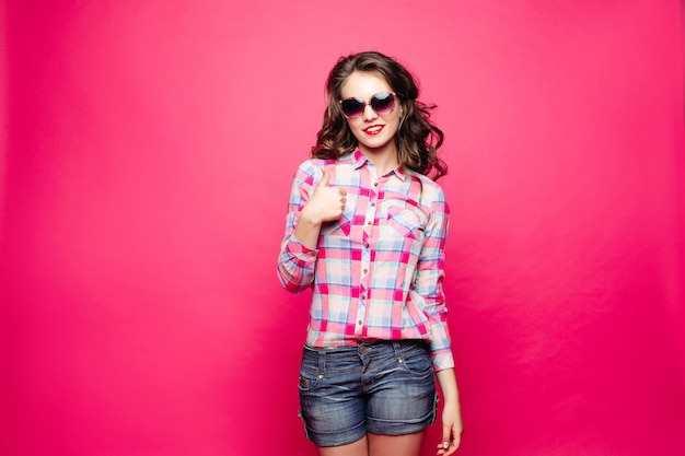 Stunning girl in shorts and shirt wearing sunglasses showing peace sign.