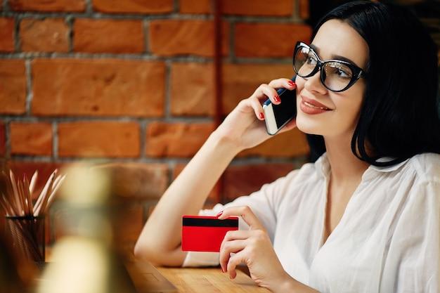 Потрясающая девушка с черными волосами в очках, сидя в кафе с ноутбуком, мобильным телефоном, кредитной картой и чашкой кофе, внештатной концепцией, покупками в интернете, в белой рубашке.