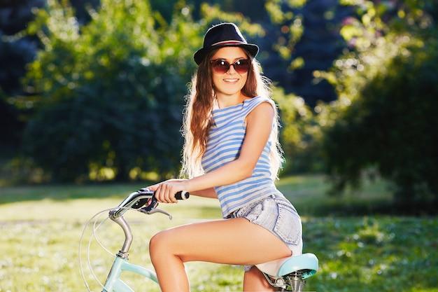 모자, 위쪽 및 공원에서 자전거와 함께 서있는 반바지, 여행, 초상화를 입고 곱슬 머리를 가진 멋진 소녀.