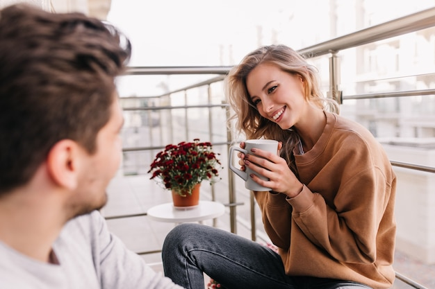 バルコニーでコーヒーを飲む巻き毛の見事な女の子。夫と一緒に身も凍るような至福の女性の肖像画。