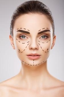 Потрясающая девушка с темными бровями на фоне студии с линиями перфорации на лице, концепция пластической хирургии, крупным планом портрет.
