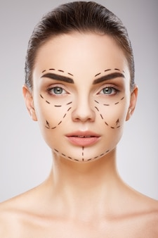 Потрясающая девушка с темными бровями на стене с линиями перфорации на лице, концепция пластической хирургии, портрет крупным планом.