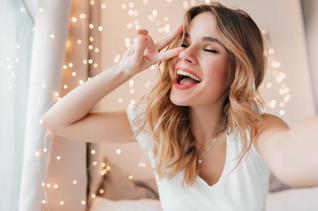 Splendida ragazza con trucco romantico in posa con gli occhi chiusi. foto dell'interno del modello femminile attraente che fa selfie nella sua stanza.