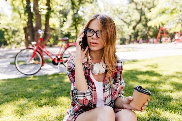 コーヒーと一緒に草の上に座っているストレートの髪型の見事な女の子。公園でポーズをとって電話で忙しいブロンドの女性の屋外ショット。